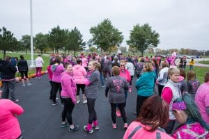 group gathers in parking lot before pink pumpkin walk