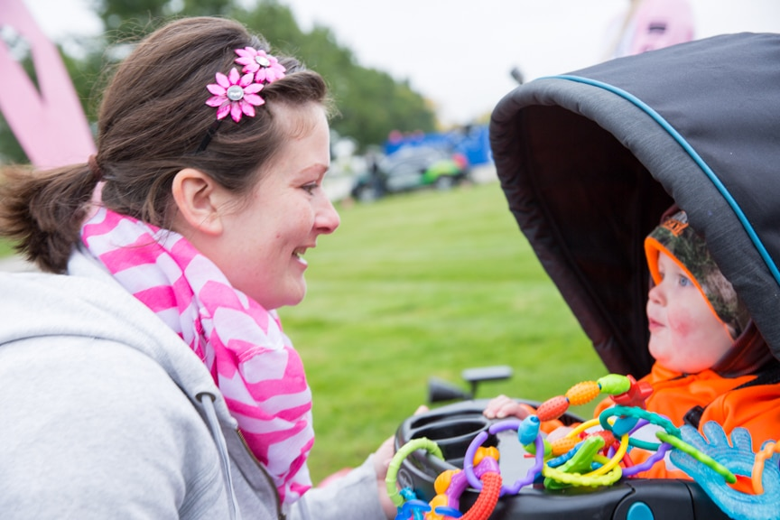 woman looks at small child in stroller at pink pumpkin walk at moraine park