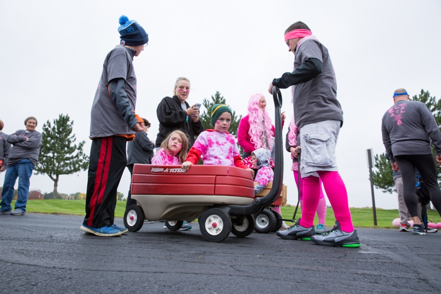 group with children in wagon waiting for pink pumpkin walk to start