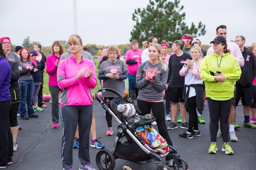 group gathers before pink pumpkin walk