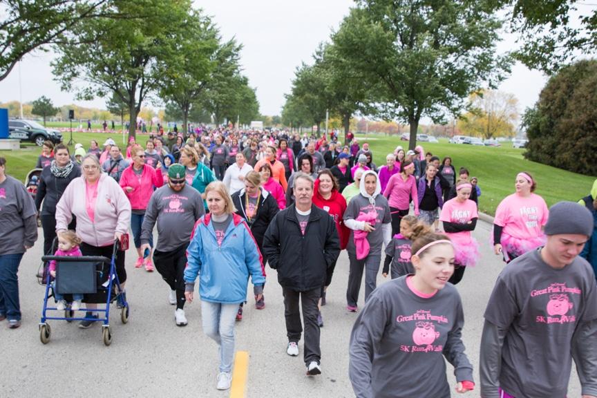 large crowd walks down street at moraine park great pink pumpkin 5k