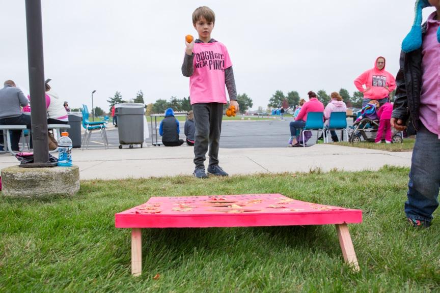 boy plays bean bag toss at moraine park event