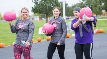 women carry pink pumpkins at moraine park