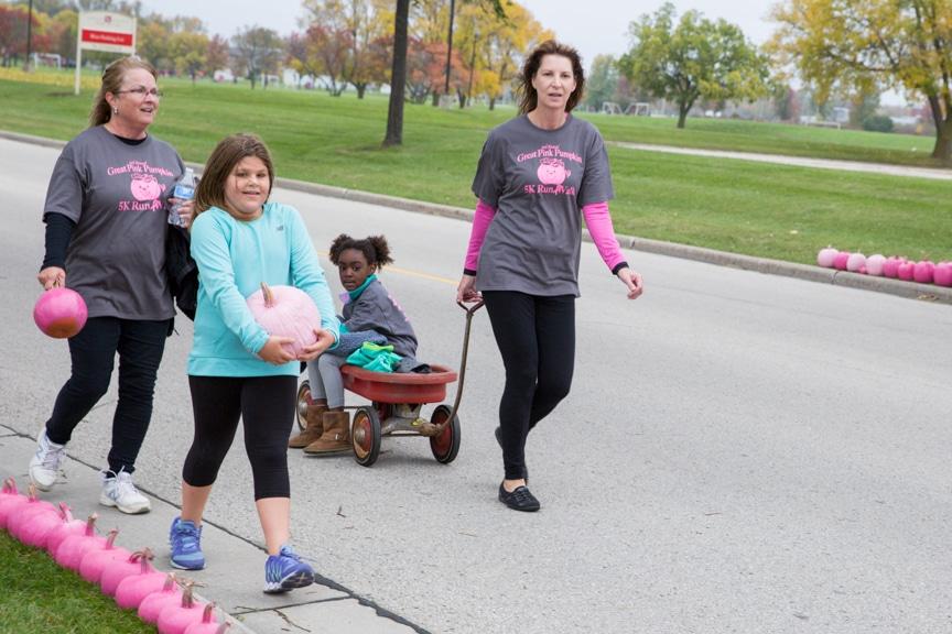 woman pulls child in wagon during moraine park pink pumpkin walk