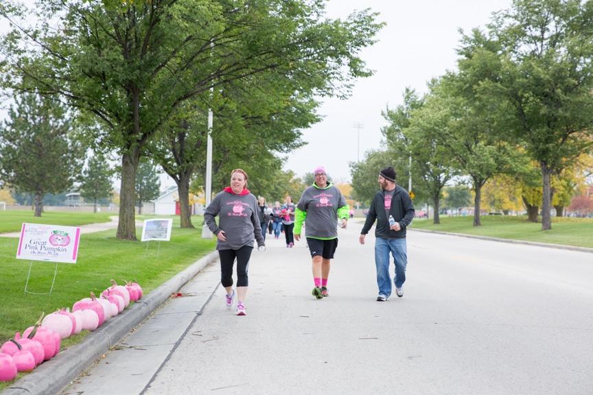 group walks down street during pink pumpkin walk