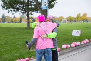two people hug during pink pumpkin walk