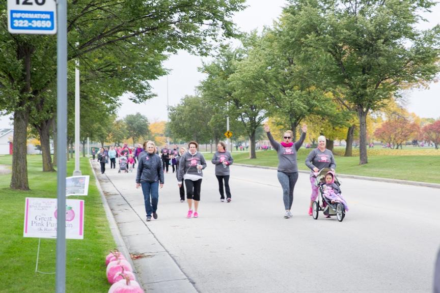 group of people walk down street during moraine park pink pumpkin 5k
