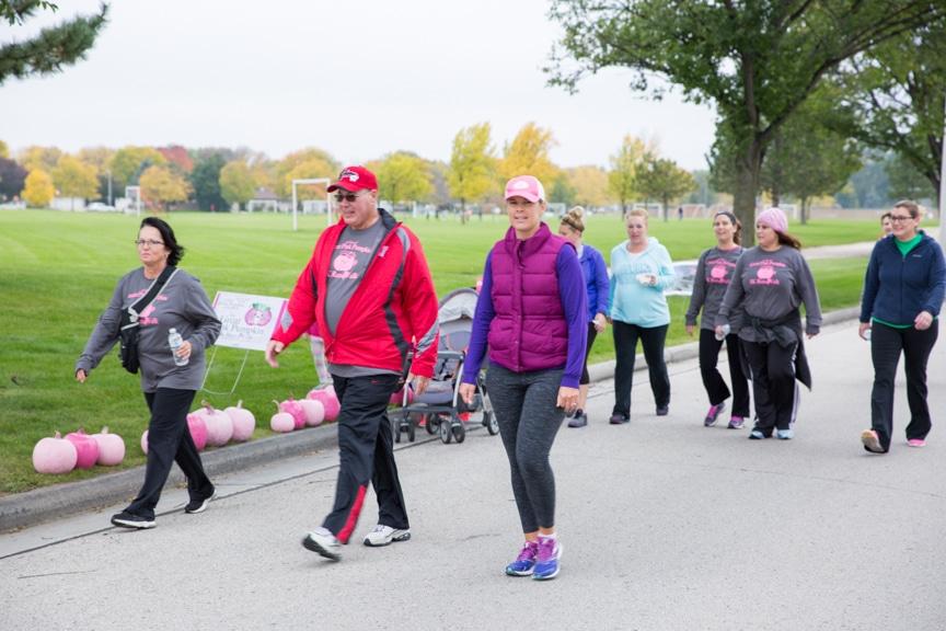 group walks down street during great pink pumpkin walk