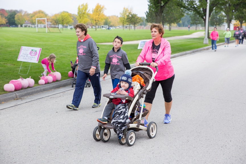 woman pushes child in stroller at pink pumpkin walk at moraine park