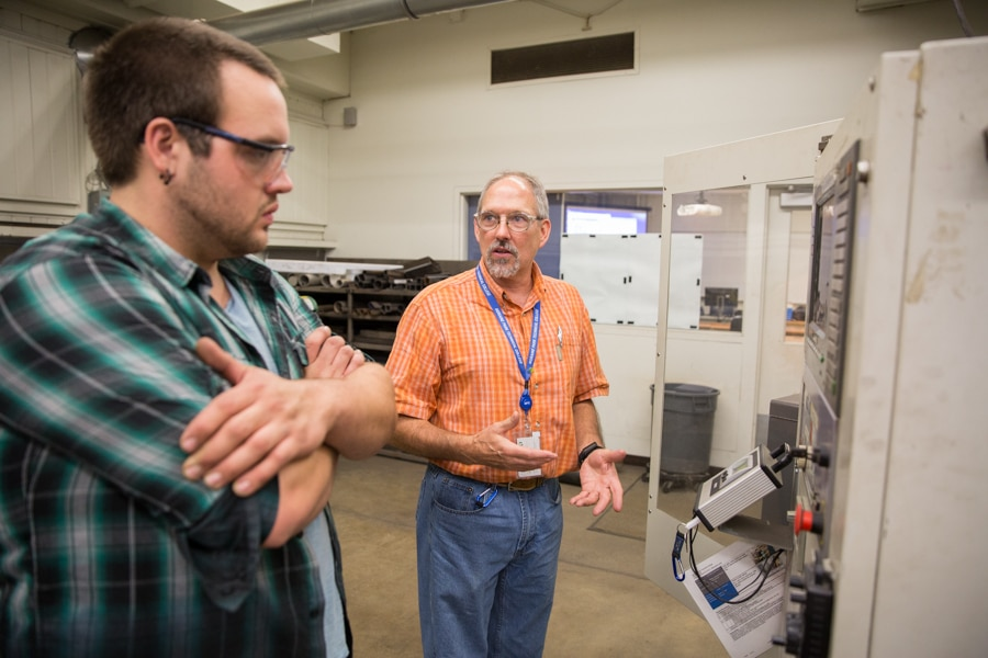 male student and instructor discussing metal fabrication machine at moraine park