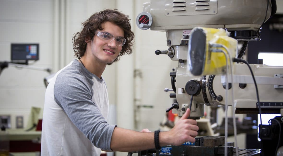 Moraine Park male student working with manufacturing machinery