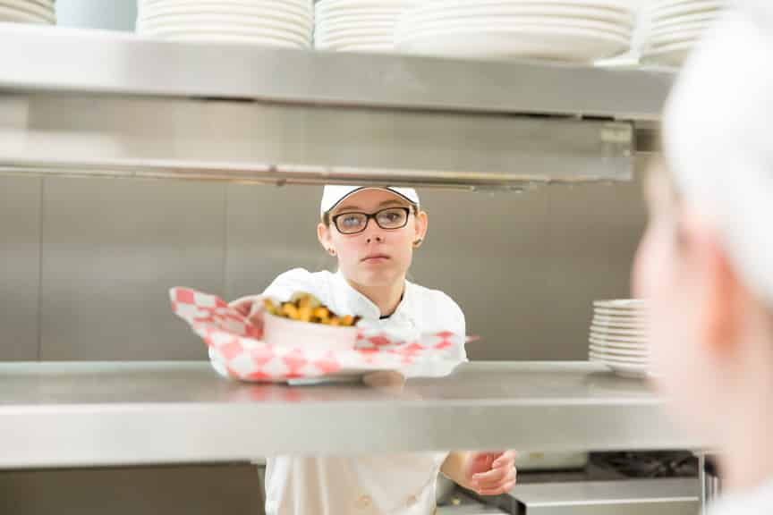 Moraine Park culinary student putting order up in kitchen