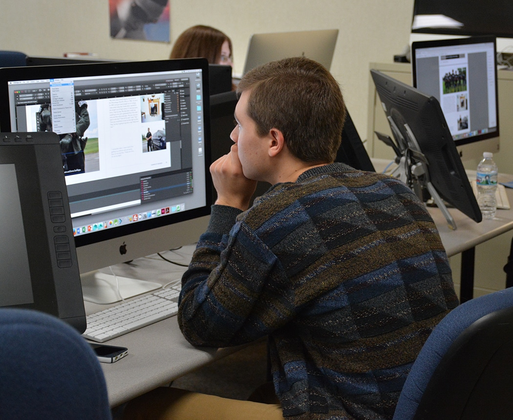 """Moraine Park male student creating page for """"Humans of Oshkosh"""" book"""