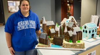 Culinary student displaying gingerbread house