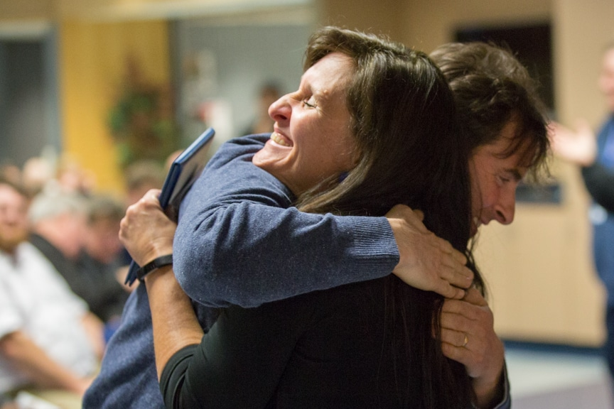 Student receives hug after receiving certificate at Boot Camp
