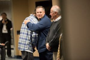 Student receives handshake and hug at Boot Camp graduation