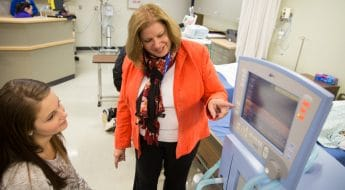 Moraine Park Respiratory Care Instructor, Mary Bandler pointing to monitor screen