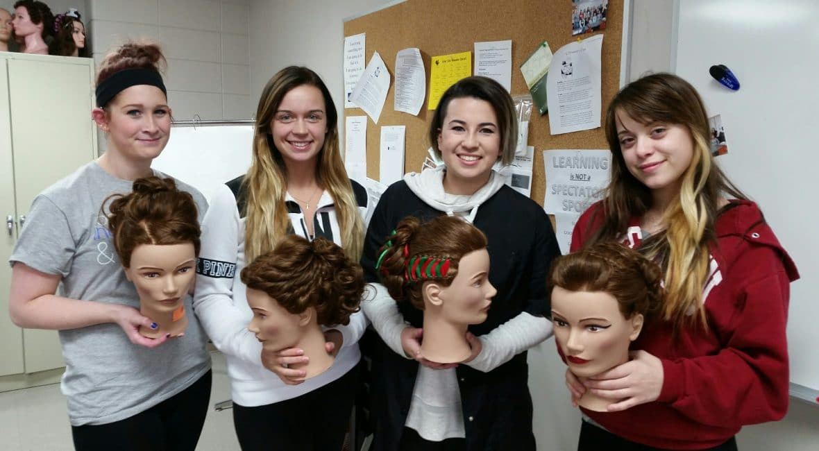 Four female Cosmetology students holding mannequin hair styles
