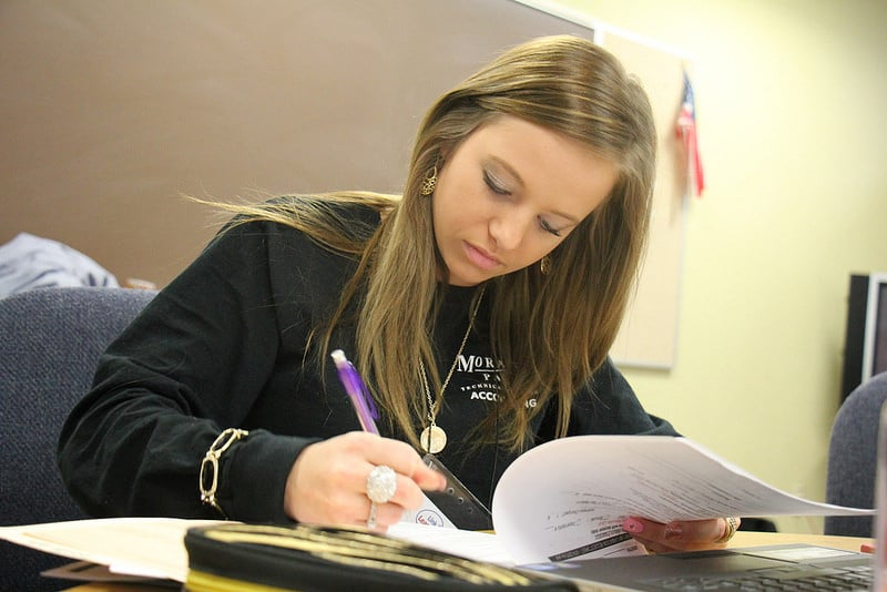 Moraine Park female student doing paperwork at desk