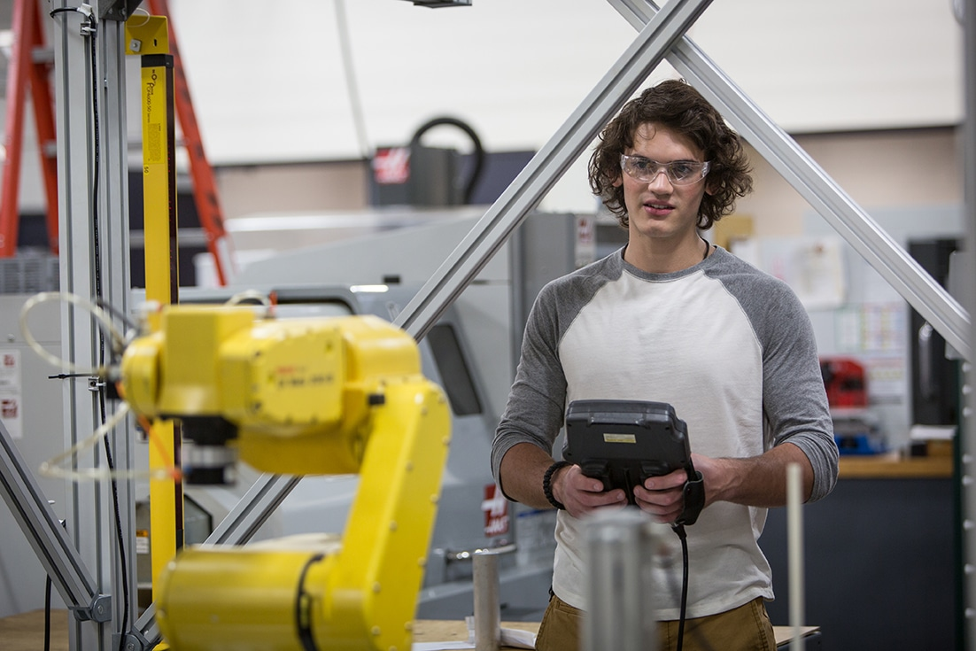 Moraine Park male student working on manufacturing equipment