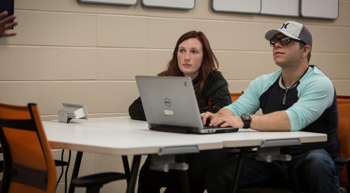 Male and female Moraine Park students working on laptop in class