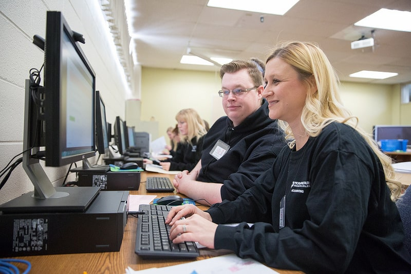 female and male accounting students work on forms on computer
