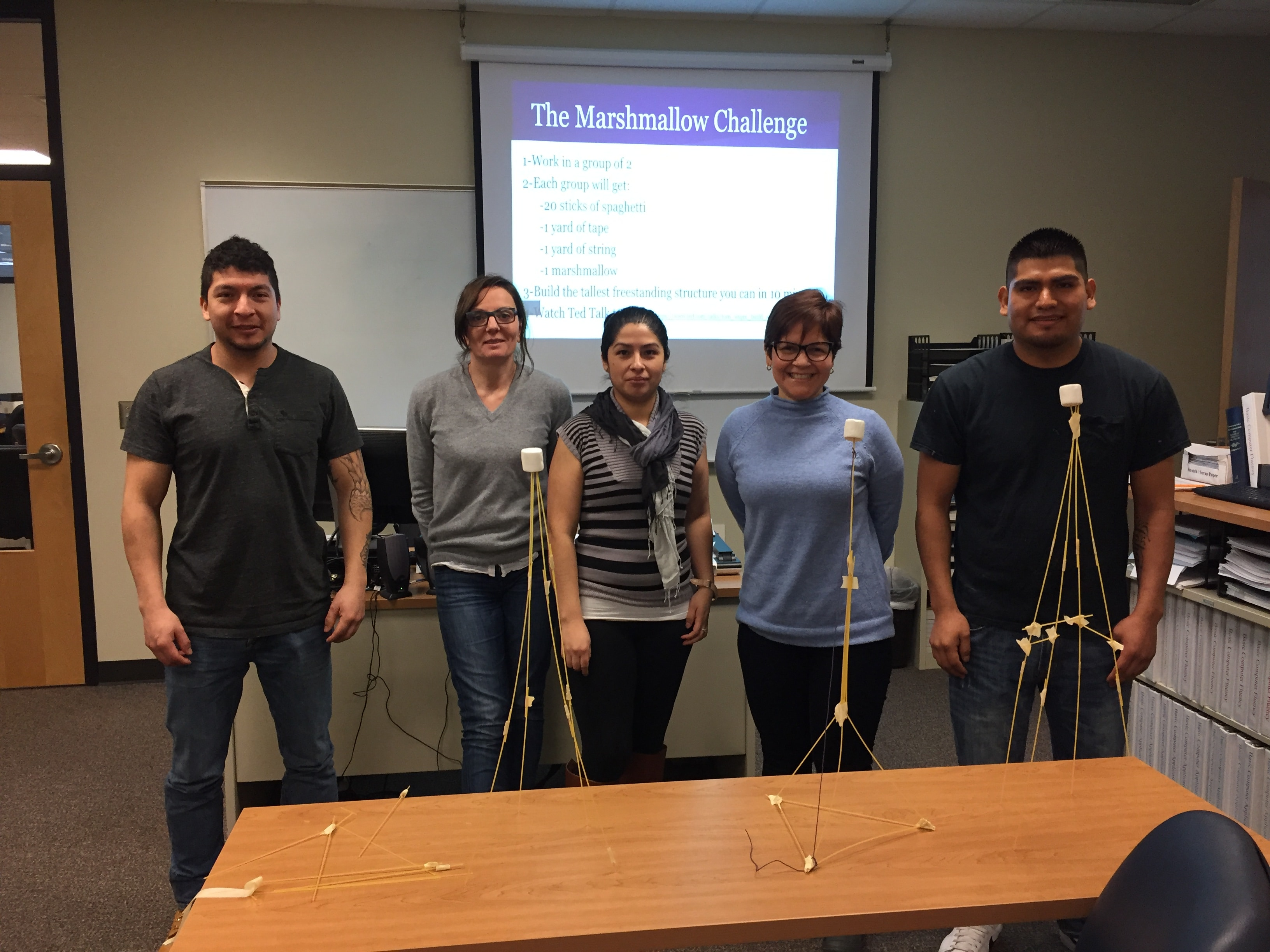 Three female and two male Moraine Park ELL student displaying their marshmallow challenge