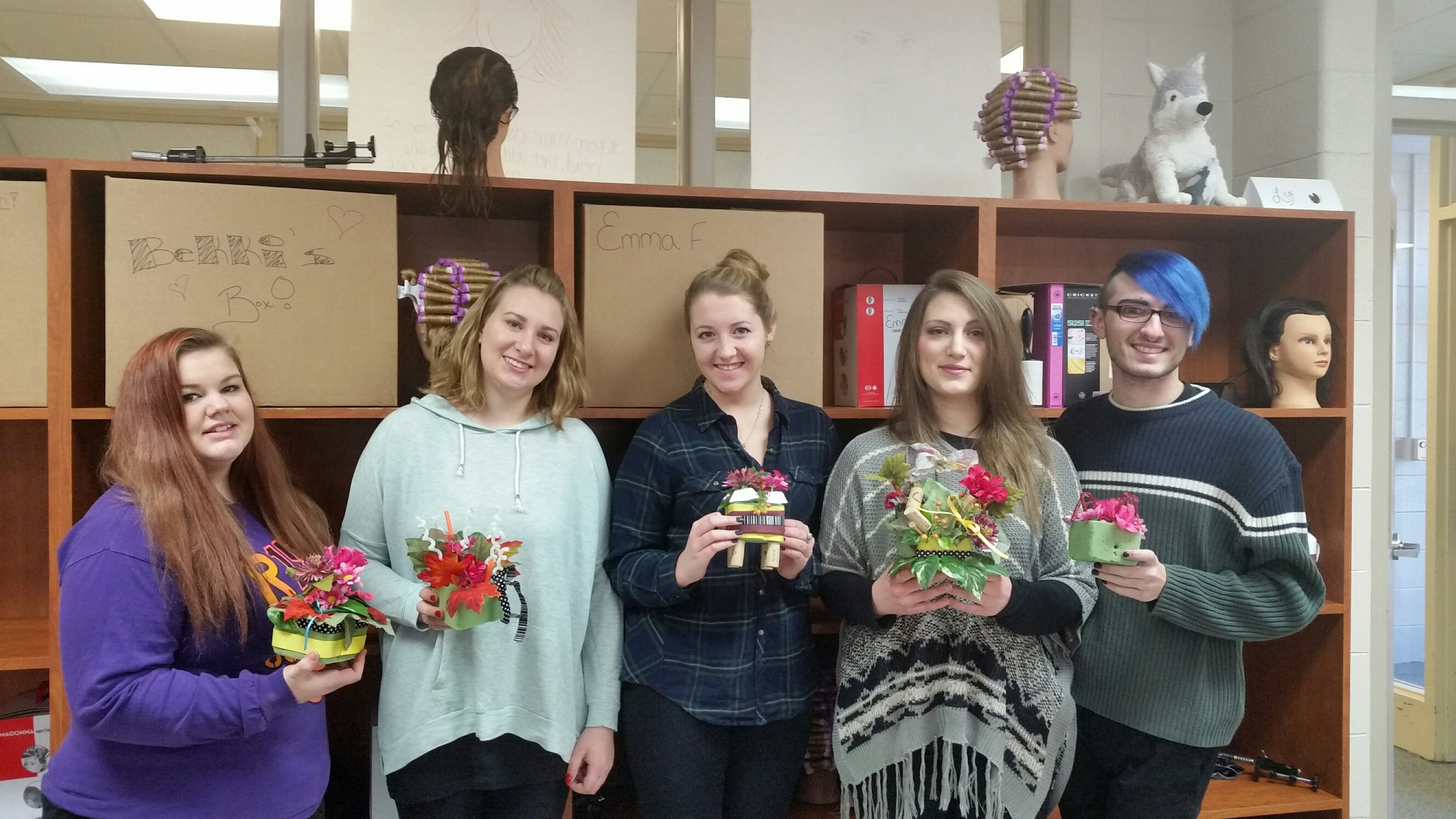 Cosmetology Moraine Park students holding artwork creations