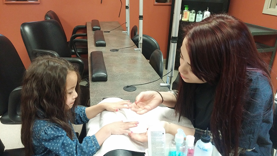 two female students at moraine park do manicures