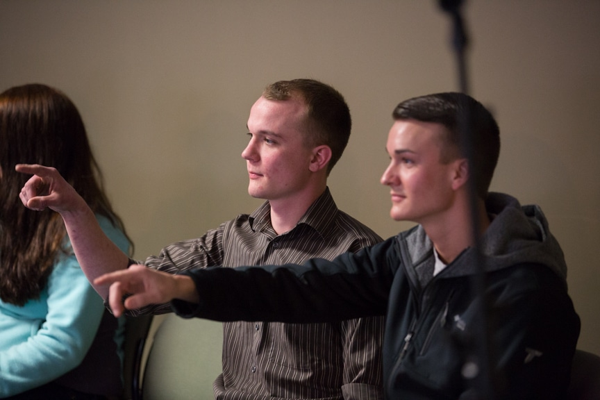 two male students point arms during chris jones hypnotist show