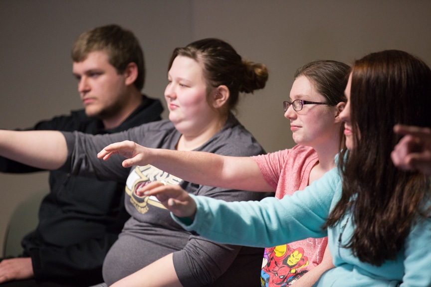 row of seated students put arms out during moraine park hypnotist show