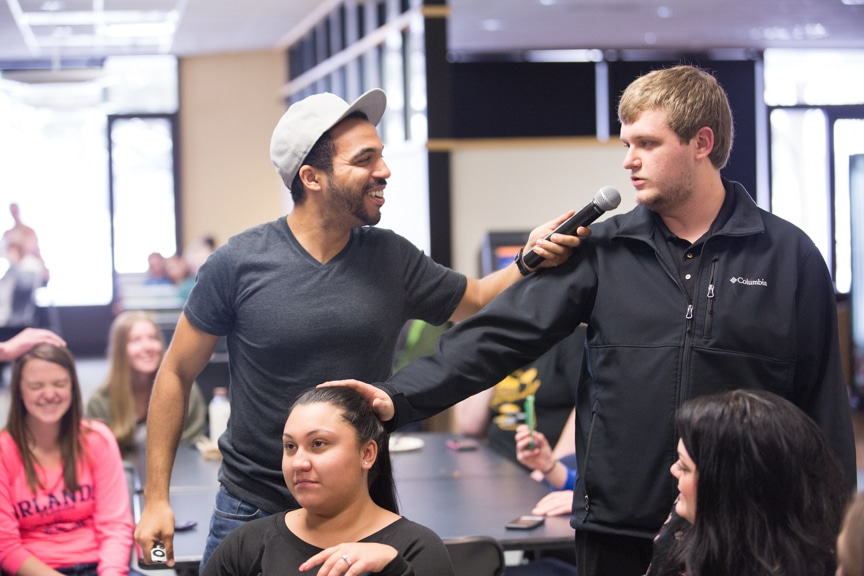 chris jones talks to male student during hypnotist show