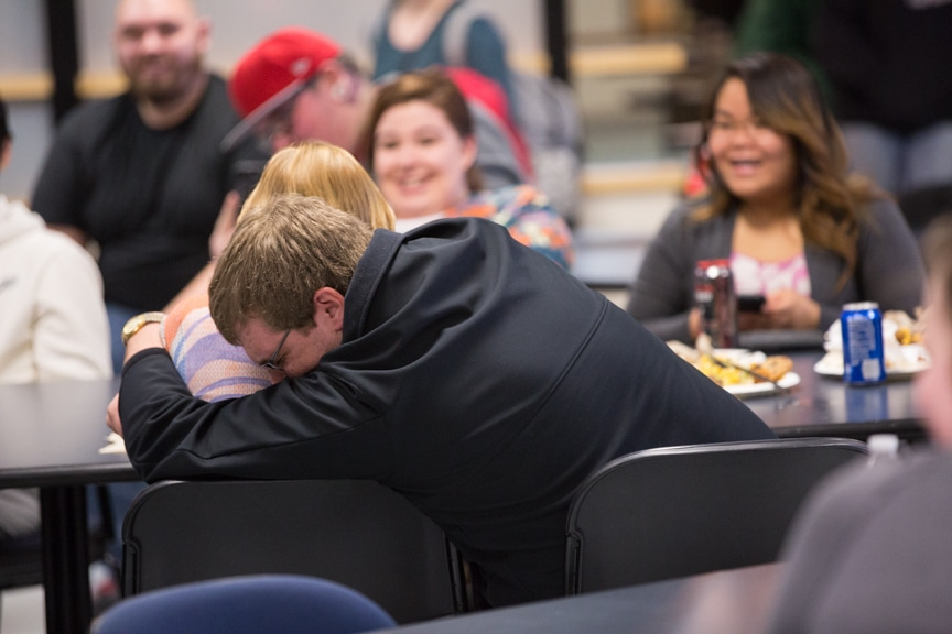 student hugs another student during mptc hypnotist show