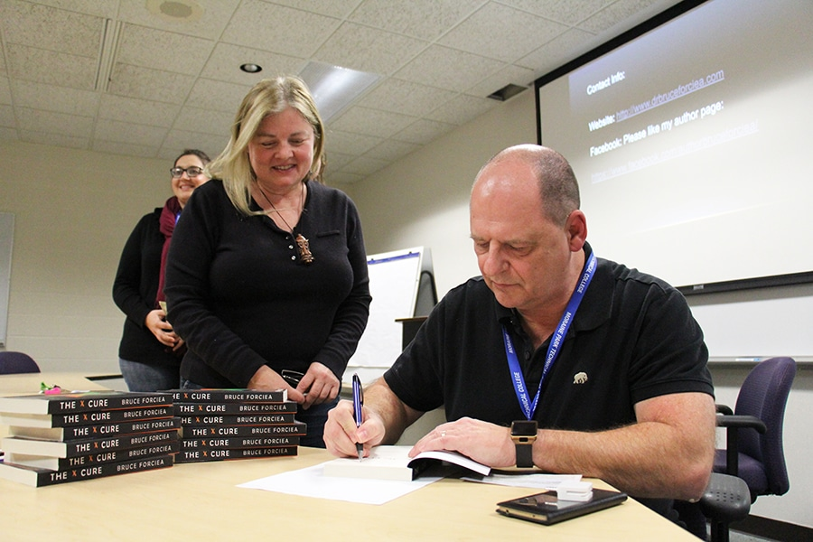 moraine park instructor bruce forcia signs copy of first novel