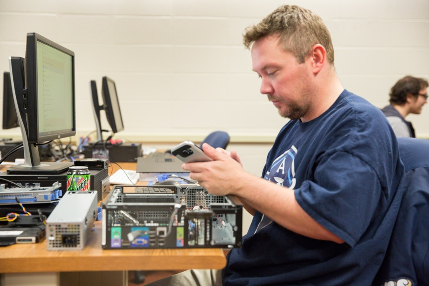 male student works on computer repair project