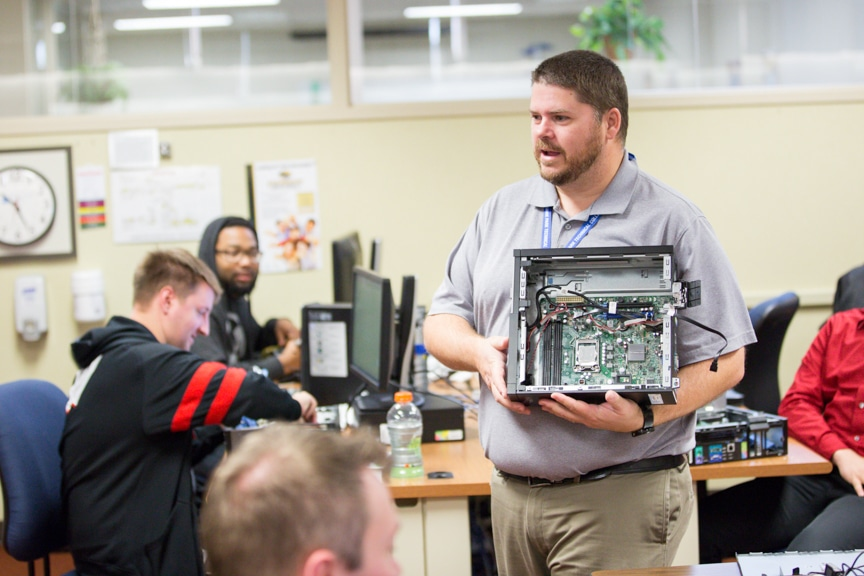 male IT instructor holds up PC computer tower to show students