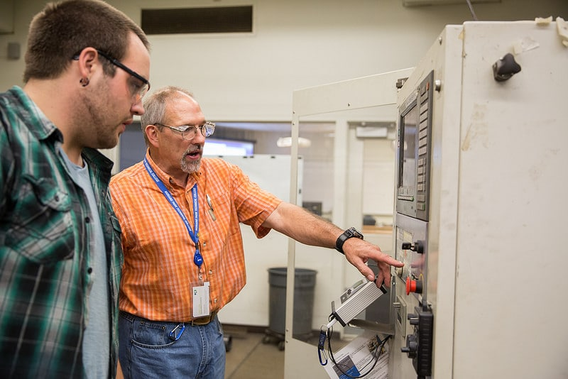 Instructor works with student in metal fabrication