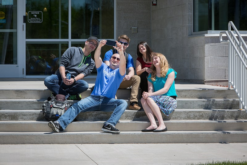 Moraine Park students taking a selfie on steps of front entrance of campus