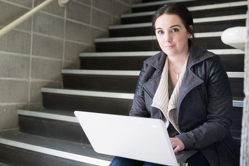 Female Moraine Park student sitting on steps using laptop