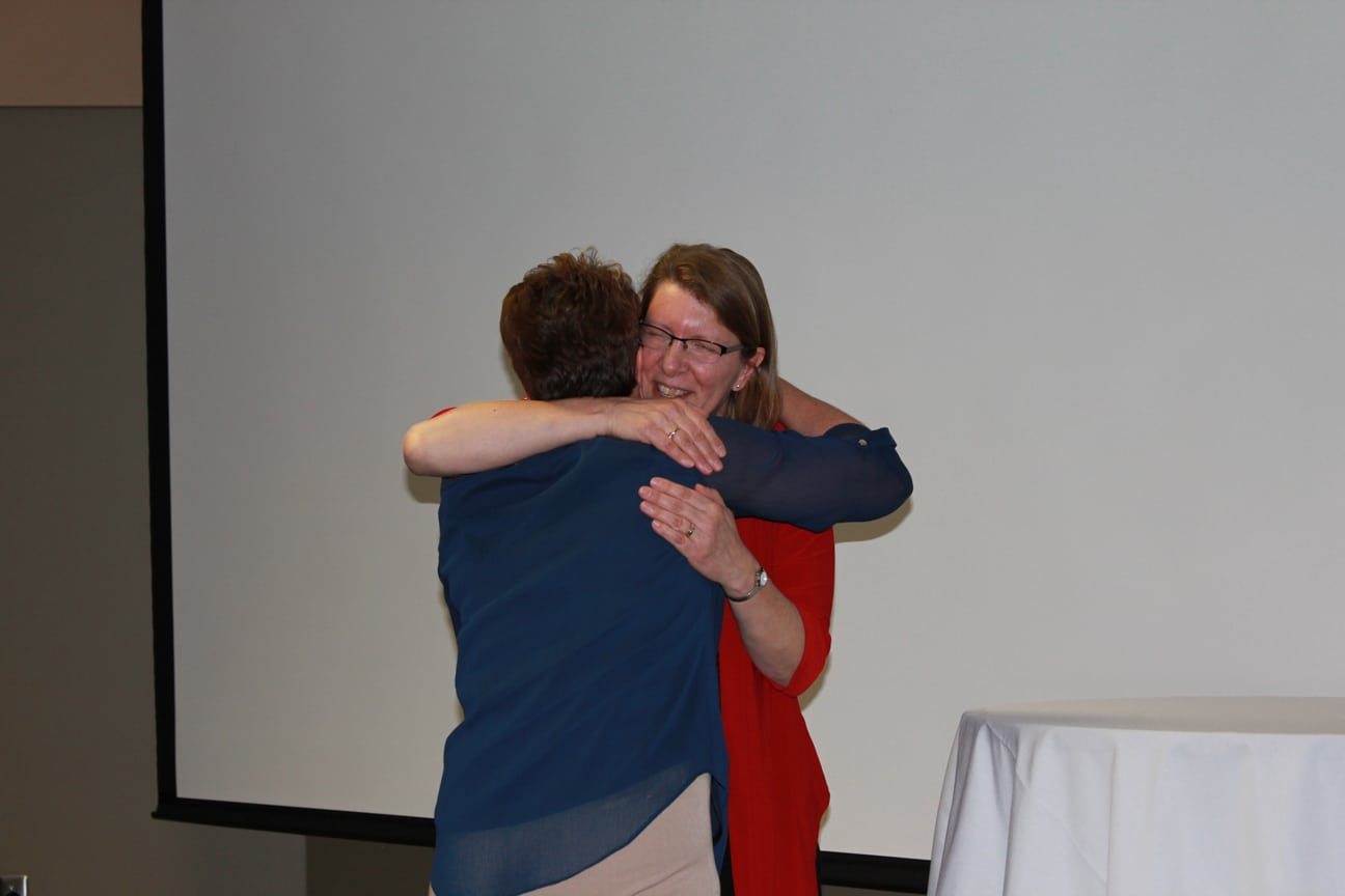 Two females hugging at event