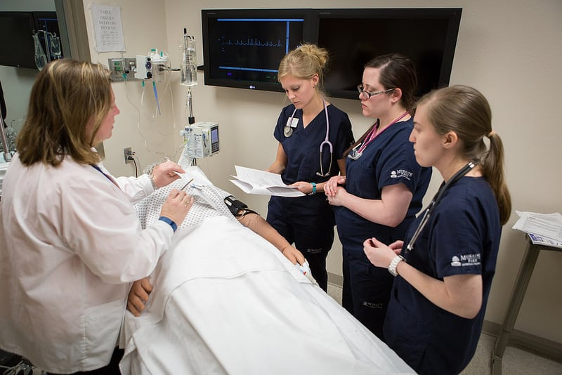 nursing instructor talks to students in simulation area