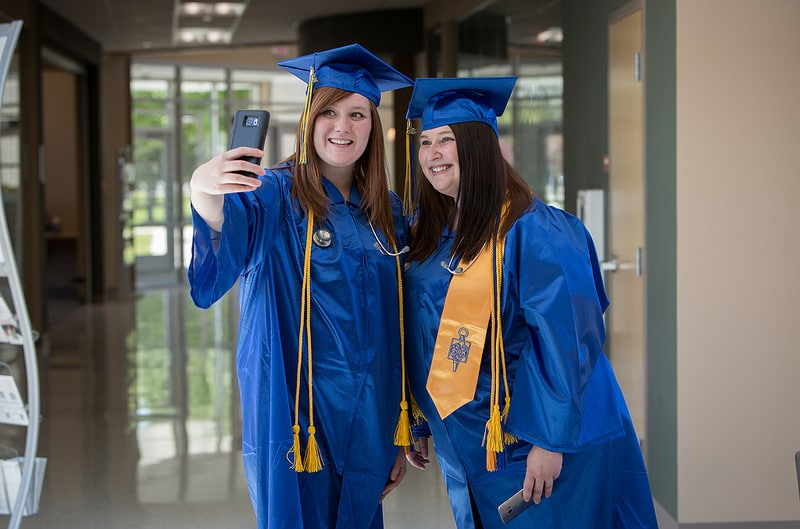 two moraine park female students take selfie in graduation cap and gown