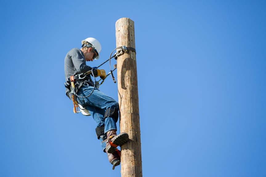 electrical power distribution student rests near top of pole in Beaver Dam