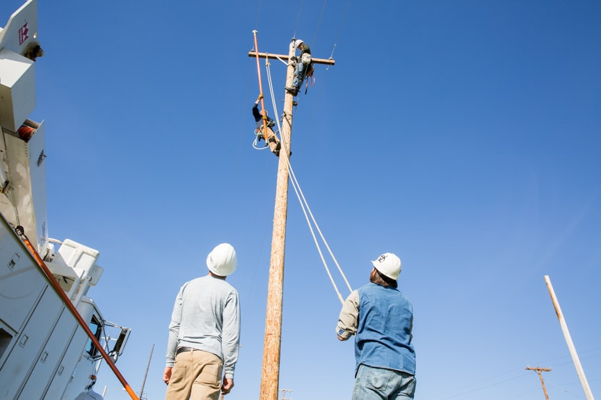 electrical power distribution work on power pole while classmates watch from below