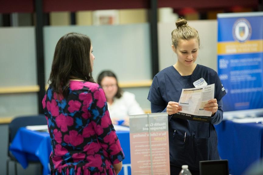 female student looks at information sheet at moraine park healthcare career fair