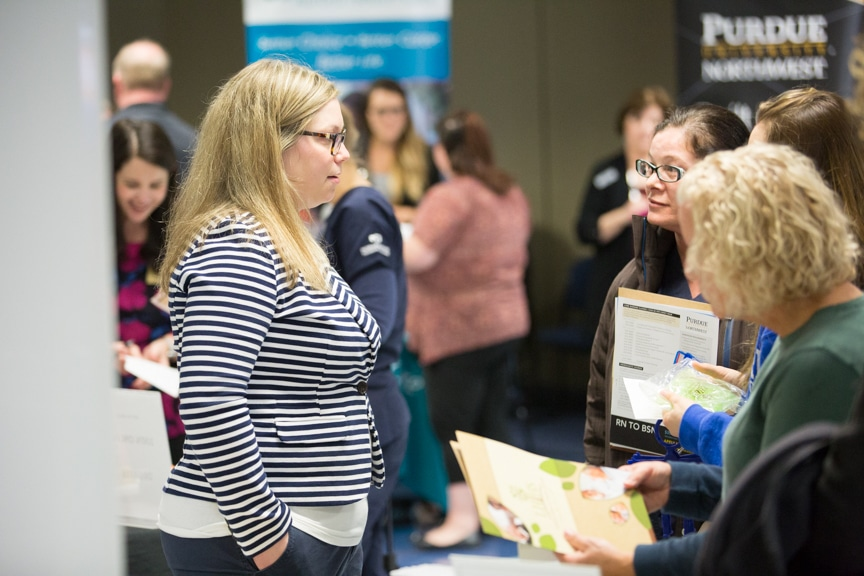 exhibitor talks with group of people at mptc healthcare career fair