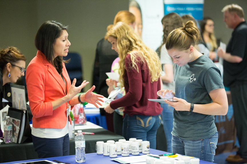 exhibitor talks with female student at moraine park healthcare career fair