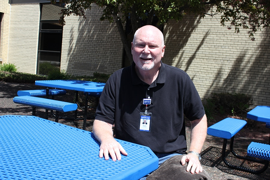 instructor mark schmidt sits outside at table