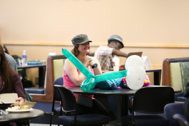 student sits with balloons at moraine park comedy show