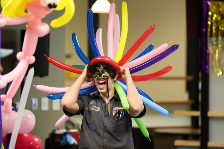female student wears large balloon hat at moraine park last blast comedy show